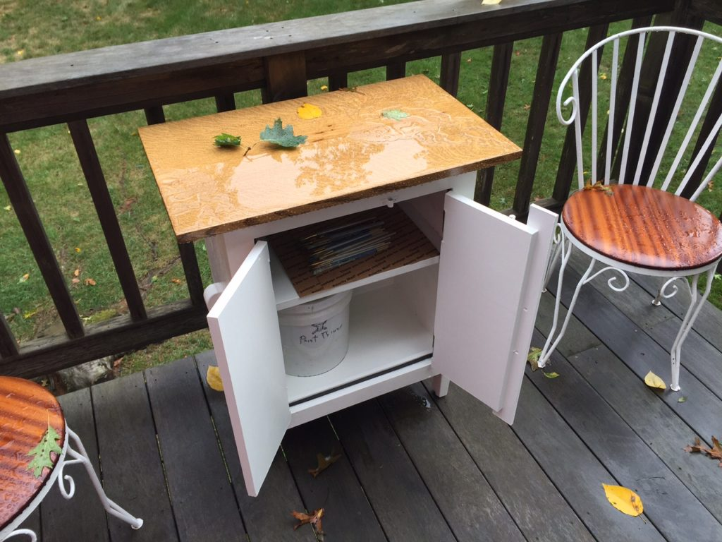 The finished cabinet after some rain with paint thinner bucket inside. It also looks good with wine inside!
